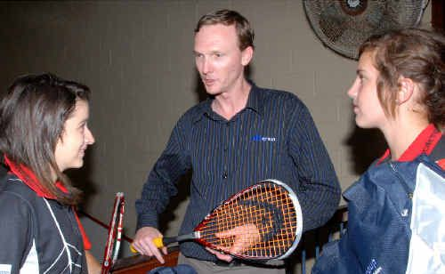 Daryl Bryce, Mackay manager of Abi Group, presents Mackay squash players Tiffany Loss, left, and Rebecca Baum with travel bags.