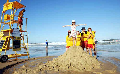 Maroochydore volunteer Lifesavers build a sandcastle with young Jazlyn on Maroochydore Beach.