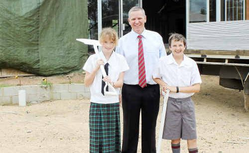 Scots PGC students Carleesha Curtis and Matthew Conn with principal Michael Harding outside the new BER library, with MBC Constructions set to rebuild the new boys' dormitory which was destroyed by fire last year (inset).