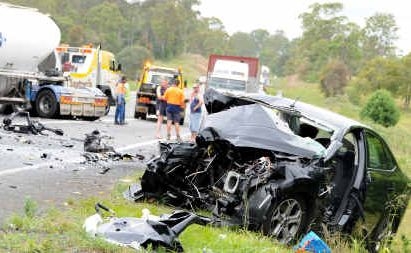 The driver of a crumpled Ford is fighting for her life in Royal Brisbane Hospital after colliding head-on with a B-Double at the site of a road side memorial for Rachel Purdy and Corey Whitmore, two of the victims of a triple fatality on September 4, 2008.