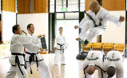 Taekwon-do black belt Greg Santos, of Bundaberg, launches a flying kick watched by instructor, Senior Master Robert Lai, in background. Helping are, from left, Jackson Lau, Christopher Camp, Kris Richardson and Bryan Beilby.