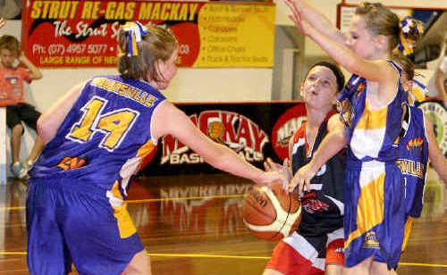 Under-12 Mackay Meteorettes player Demi Baker looks for the hoop, under pressure from Townsville Flames' Majella Caret and Gracie Dale.