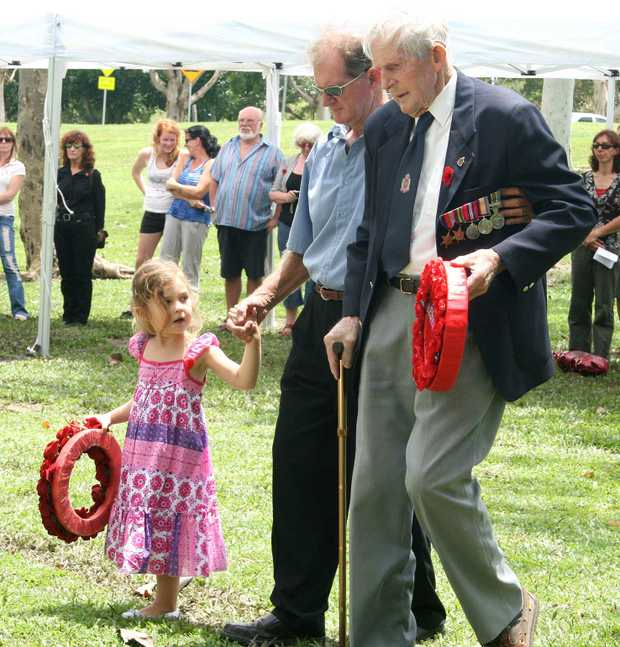 Little Krysta Fahey,3, helped her poppy and ex Navy chief Peter McKellin and WWII veteran Jack Payne up to the cenotaph to lay their wreaths on Remembrance Day