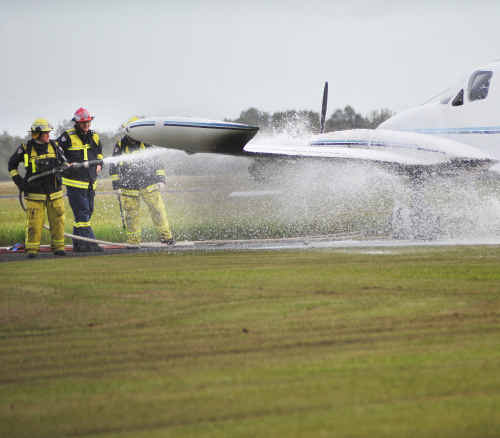 Firefighters extinguish the port side engine of an aircraft that caught fire at the airport .