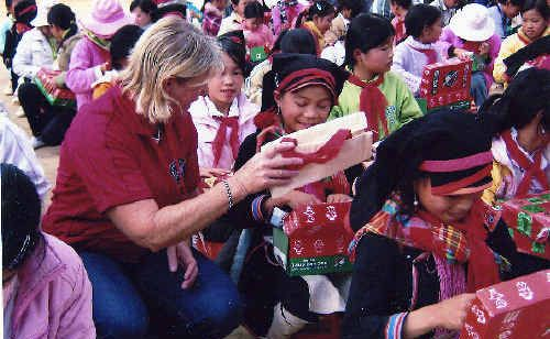 Judy Burrows giving out Christmas boxes to children in Vietnam.