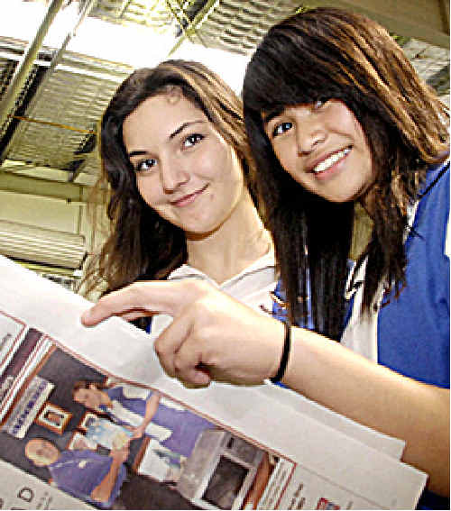 Looking through their newspaper are Laura Beltramy (left) and Kathryn Pamogas.