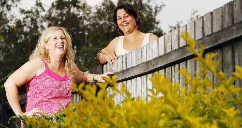 Neighbours Jo Pask and Sandra Reid share a joke over their backyard fence.