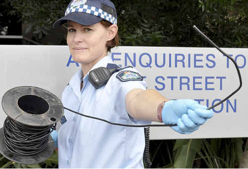Toowoomba Police officer Constable Rachel Doljanin inspects the electrical cable which was removed from between two power poles across an East Toowoomba street.