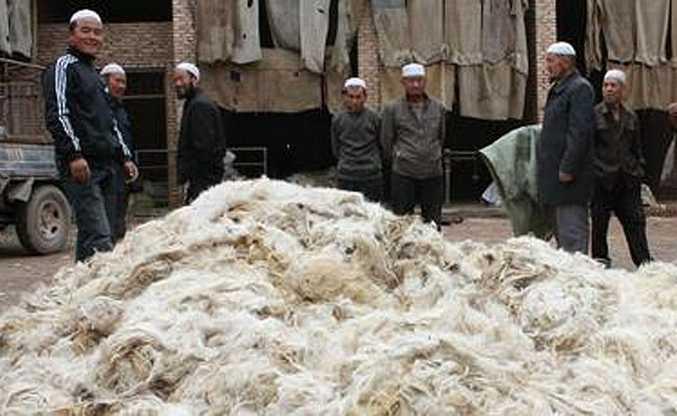 Hui men selling wool at a village market in China.