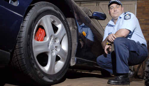 Toowoomba police traffic branch officer Sergeant Brendan Harding inspects a vehicle impounded for hooning.