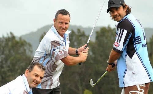 Woolgoolga coach Greg Shuttleworth, kneeling, helps Chris Seymour and Clark Webb prepare for the club's annual golf day.
