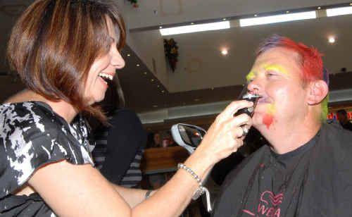 Caneland Central shopping centre shopper Jo-Anne Hunter shaves off the moustache of Mackay Senior Constable Simon Robinson.