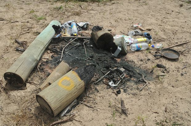 The remains of several large treated timber bollards, burned in the sand dunes along Boambee Beach.