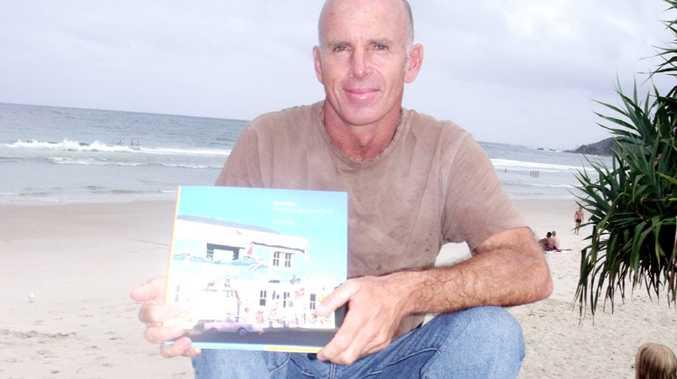Peter Duke at Main Beach Byron Bay with his new book, 'Byron Bay The History, Beauty and Spirit'.