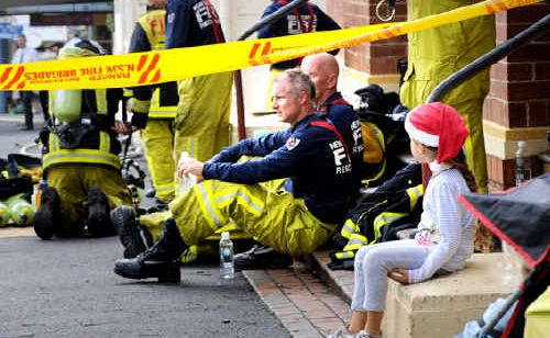 Sophie Ward, 5, sits behind the fire tape in Byron Street, Bangalow, near firefighters taking a break from fighting the blaze.