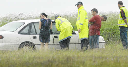 Police, witnesses and tow truck drivers attend a vehicle that was driven off the Warrrego Highway into a paddock at Charlton on Saturday.