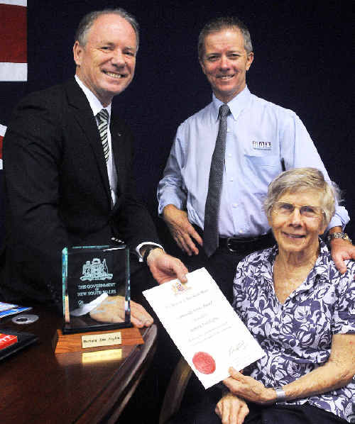 Barbara Hogbin with her NSW Government Community Service Award, Coffs Harbour MP Andrew Fraser and Barbara's son, Ian Hogbin.