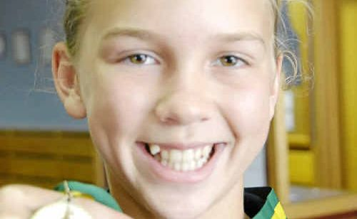 Anthea Moodie,10, is all smiles after winning the high jump at the School Sport Australia 12-and-under Track and Field Championships.