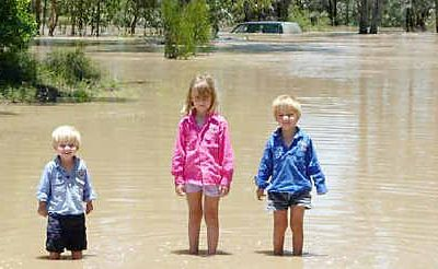The Ramsay children (from left) Cooper, 2, Ally, 5, and Brodie, 4, spent three hours trapped on the roof of their family four-wheel-drive (in background) with parents Brett and Stacey after it was washed from Humbug Road into Undulla Creek about 25 kilometres west of Tara.