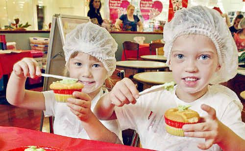Four-year-old twins Olivia and Jackson Patterson taking part in the Christmas cupcake workshop at Redbank Plaza on Monday.