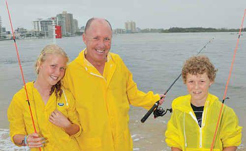 Brisbane's Darren Teale with his children Sarah-Rose, 12, and Adam, 10, weren't deterred by the rain at Cotton Tree yesterday.