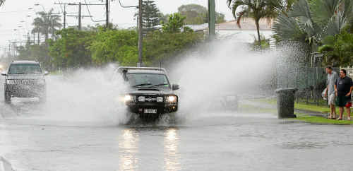 Alexandra Street residents get a drenching as a four-wheel drive ploughs through the rain water which fell during a heavy fall about 11.30am.