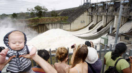 Cooper Paris, 7 months, of Rothwell gets a boost from his dad as five spillway gates open at Wivenhoe Dam.