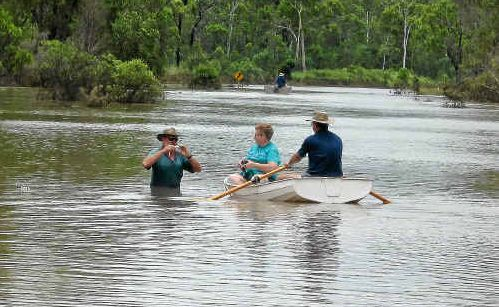 """Frank McKee, in the water, of the southern end of Monto Road meets Albert and Judy Spencer (in boat) from the northern end of the road during Thursday's """"party"""" meeting."""