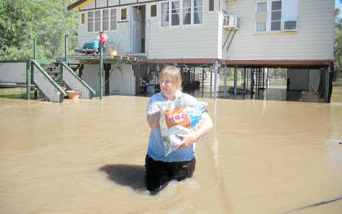 Condamine resident Loretta Eather wades through floodwater in front of her home before being evacuated.