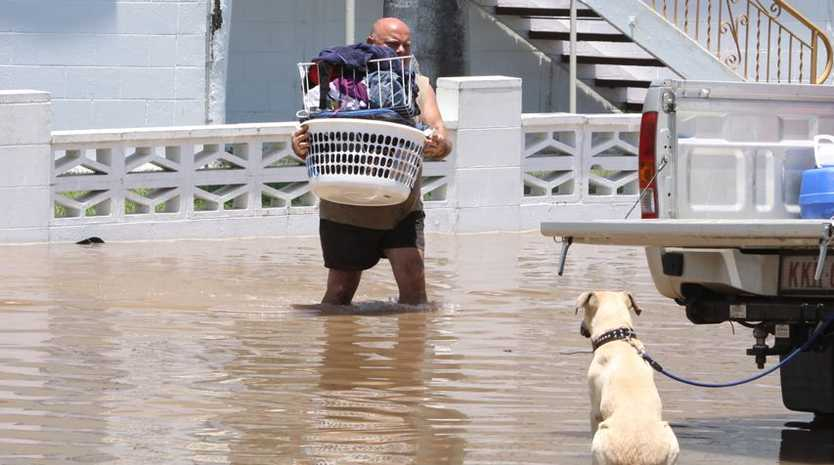 A man packs his belongings into the back of a ute during the floods in Rockhampton.