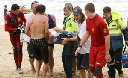 Ignored flags: A man is pulled from the surf at North Shore yesterday.