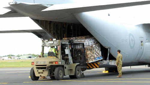 Australian Defence Force personnel unload crates loaded with emergency supplies bound for Rockhampton at Mackay Airport yesterday afternoon.