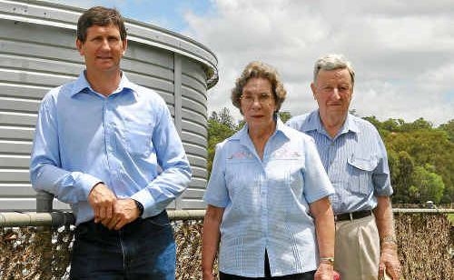 Deputy Leader of the Opposition and Local Member Lawrence Springborg and Save Our Slade committee members Margaret and Neil McKinnon near the school oval fence with flood debris.