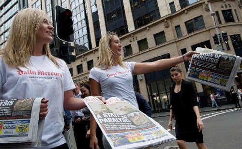 Elkie and Kara hand out free copies of the Daily Mercury outside the Australian Stock Exchange in Sydney's CBD.