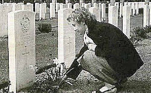 An unidentified woman visits the fallen airman's grave, in a Dutch ceremony, two years after the war.