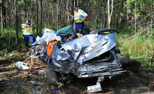 Police examine the wreckage of a fatal crash on the Pacific Highway near Tabbimobile. Photo: ADAM HOURIGAN/The Daily Examiner.
