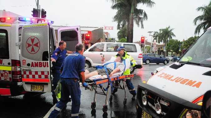 Ambulance paramedics help one of the three men who have been stabbed at the Coffs Harbour Hotel tonight.