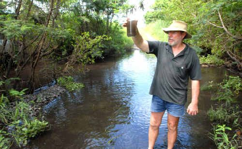 Peter Dallas with a sample of the black water he says was polluting mangroves at Hay Point.