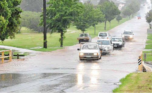 Cars navigate carefully through flash flooding on Alderley Street.
