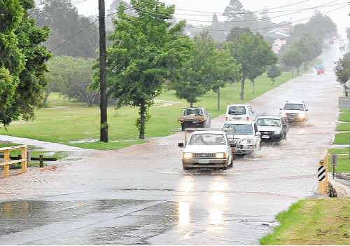 Cars navigate carefully through flash flooding on Alderley Street.