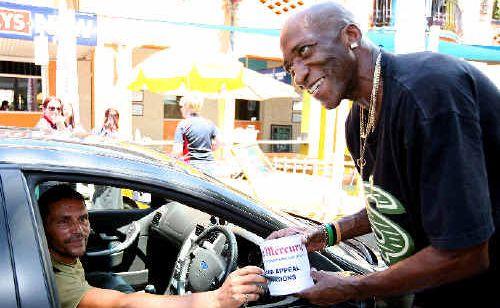 """John Silarsah stops to donate to """"Sir Reg"""" Biddings."""