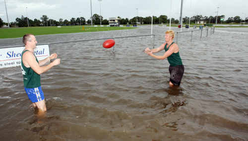 Maroochy Roos train despite the rain flooded fields, here Shaun Fletcher and Greg Stirton get some handball practise in before taking a road run.