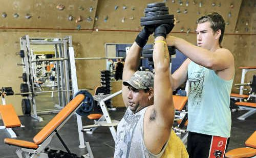 Ian Ell spots for Joel Tanna in the gym during a weights session.