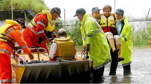 Rescue crews help Goodna resident Maureen Evans on Woogaroo St, Goodna yesterday.