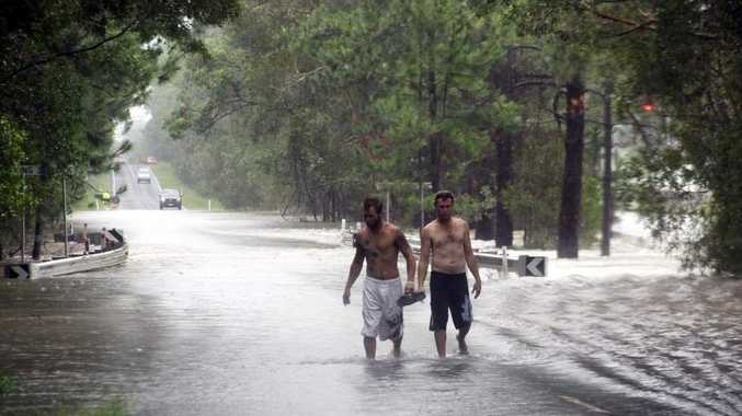 People walk through flooded parts of Beerburrum Road  to test the height of the water as it runs across the flooded road.