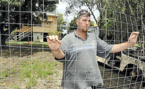 Clinton Wright stands at the back fence of his home in Alexandra Street, East Bundaberg, wondering if he will have to evacuate again.