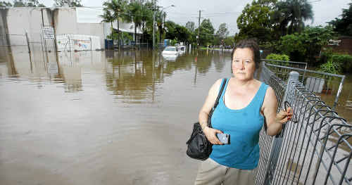 Cheryl Mackrodt heads home through floodwaters on Mill St, Goodna.