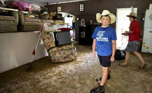 Lachlan Hill, 9, of Tabulam, helps clean one of the houses in Tabulam that was flooded with more than a metre of water from the Clarence River on Tuesday afternoon.