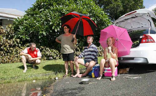 The Savage family waits at the water's edge and watches its Basin Pocket home disappear into the floodwater.