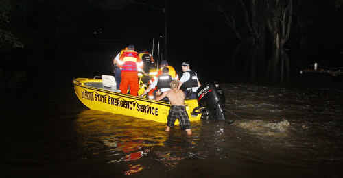 Police and State Emergency Service volunteers use boats to help a flood-stricken Creek Street resident in Bundamba.